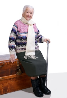 Oude vrouw zittend op een doos met een stok op een witte achtergrond