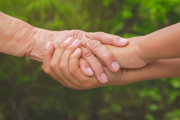 Oude vrouwelijke hand die jonge jongenshanden, zorg en steunconcept houden