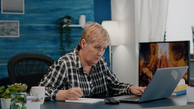 Oude vrouwelijke ondernemer die een financieel project van een bedrijf controleert dat op een laptop kijkt die jaarlijkse statistische gegevens analyseert, aantekeningen maakt op een notebook die aan het bureau zit in een woonkamerkantoor dat vanuit huis werkt