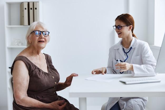 Oude vrouwelijke patiënt communiceert met de gezondheidsdiagnostiek van de arts