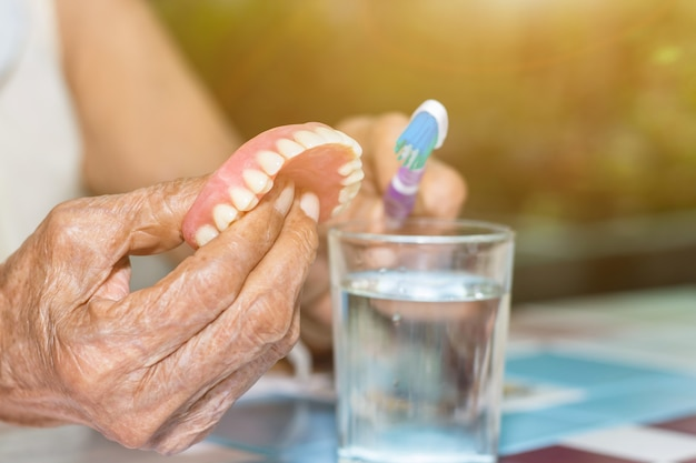Oude vrouwen houden valse tanden vast met vuil voor uitneembare gedeeltelijke prothesereiniging met een tandenborstel