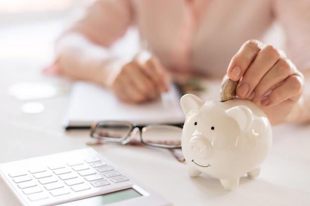 Oude vrouwenhanden zetten geldmunten in een varkentje