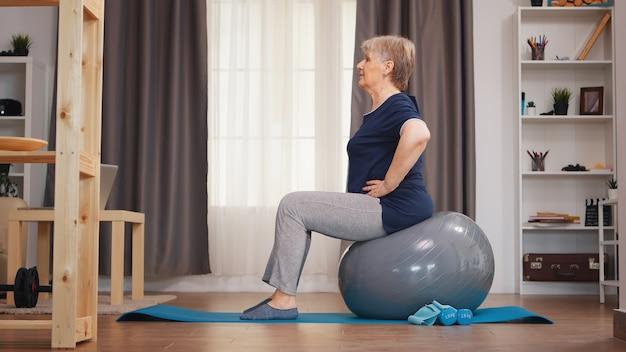 Oude vrouwentraining op opleidingsbal in woonkamer. bejaarde training thuis gezonde pensioen levensstijl stretching, thuis training en lichaamsbeweging