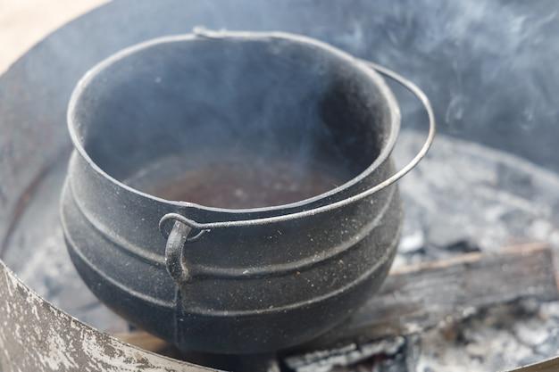 Oude vuile pot op een vuur waarin was smelt