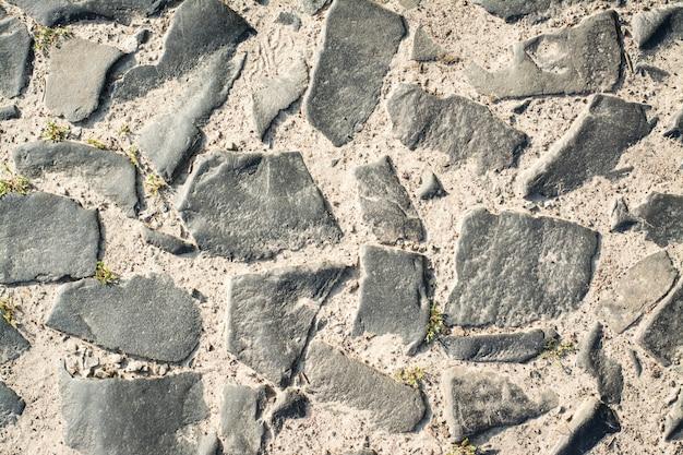 Oude weg die van kei achtergrondtextuur wordt gemaakt