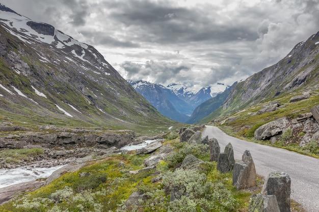 Oude weg in de bergen die door wolken in noorwegen worden omringd.