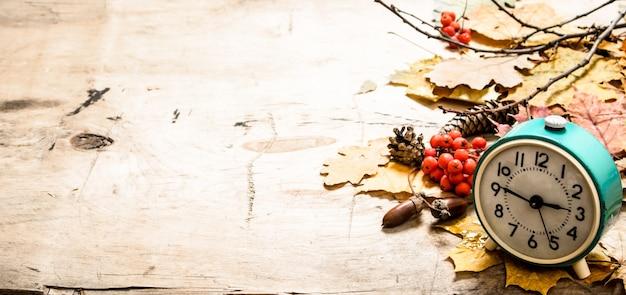 Oude wekker met herfstbladeren, kegels en bessen van lijsterbes. op houten achtergrond.