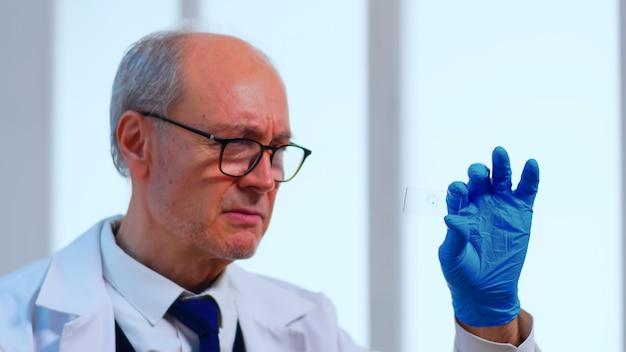 Oude wetenschapper man analyseert virusmonster in uitgerust laboratorium. wetenschapper die werkt met verschillende bacteriën, weefsel- en bloedmonsters, farmaceutisch onderzoek naar antibiotica tegen de pandemie van het coronavirus