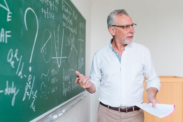 Oude wiskundeleraar die formule verklaart bij klaslokaal