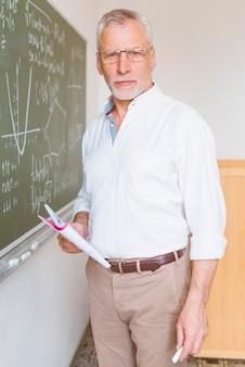 Oude wiskundeleraar die zich in klaslokaal met krijt bevindt