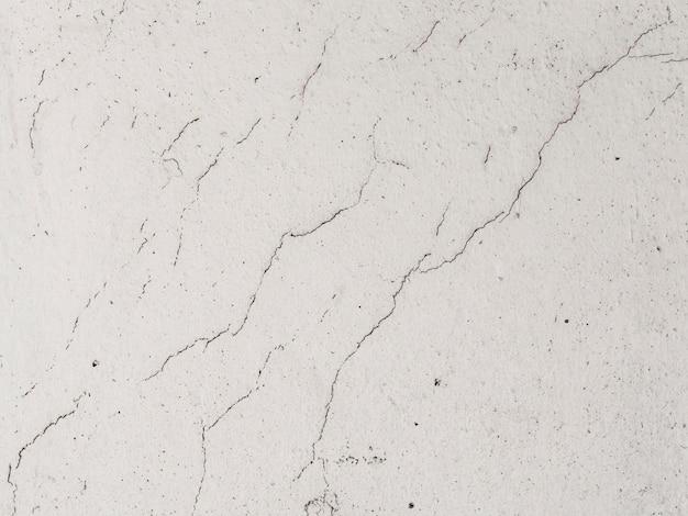 Oude witte cementmuur met gebarsten geweven