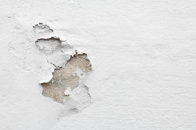 Oude witte gepelde pleistermuur