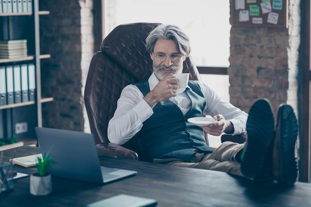 Oude zakenman kijken seminar over laptop koffie drinken in kantoor