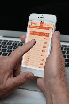 Oude zakenman met smartphone vliegtickets op mobiele app kopen