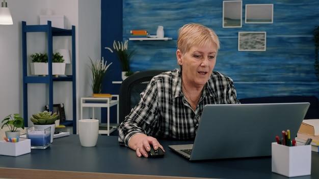 Oude zakenvrouw van middelbare leeftijd die bij laptop werkt en financiële gegevens typt