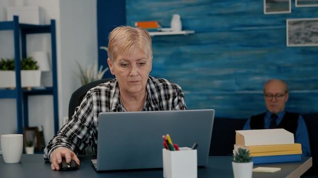 Oude zakenvrouw van middelbare leeftijd die thuis op een laptop werkt, senior volwassen vrouw die op pc financiële gegevens typt die aan het bureau zit