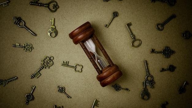 Oude zandloper en klassieke sleutels op pakpapierachtergrond