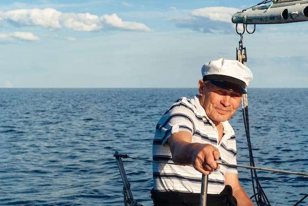 Oude zeeman op zijn zeilboot tegen een zeegezicht