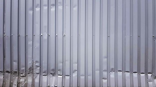 Oude zinksamenvatting. zink vintage achtergrond weergave. verfrommelde metalen plaat van het hek. tin dak achtergrond met een gat van roest en nagels vintage stijl. zink muur oppervlak detail met gaten.