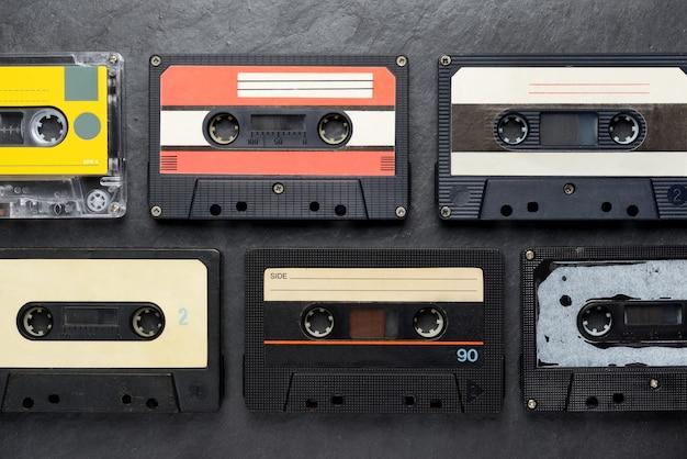 Oude zwarte audioband compact cassettes op zwarte lei