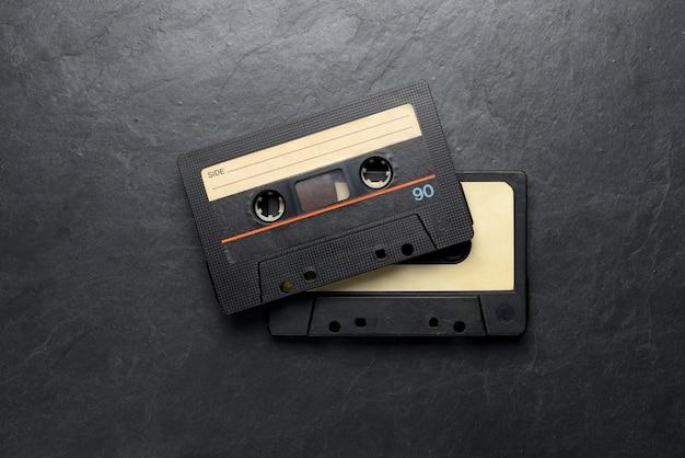 Oude zwarte audioband compactcassettes op zwarte leisteenachtergrond