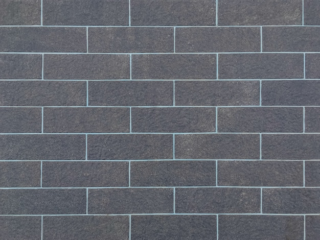 Oude zwarte bakstenen muur geweven achtergrond van de close-upoppervlakte