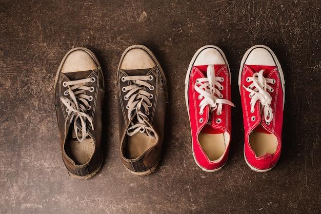 Oude zwarte en rode sneakers en op een donkere marmeren achtergrond. schoenen voor buitenactiviteiten