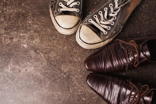 Oude zwarte sneakers en bruine klassieke schoenen op een donkere marmeren achtergrond. schoenen voor buitenactiviteiten