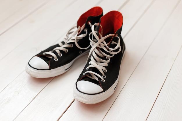 Oude zwarte sneakers met rood