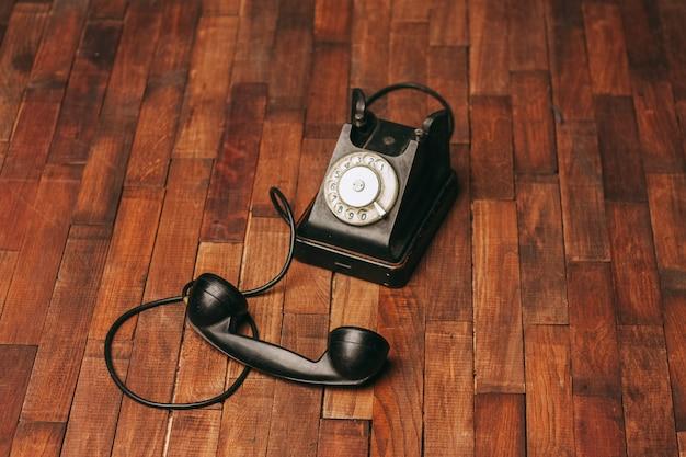 Oude zwarte telefoon op de vloer, vintage