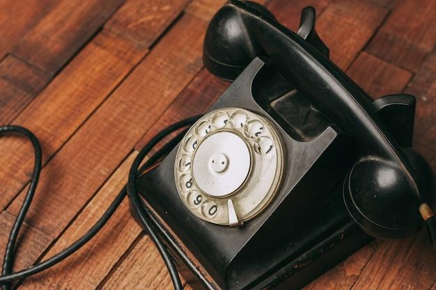Oude zwarte telefoon op de vloer