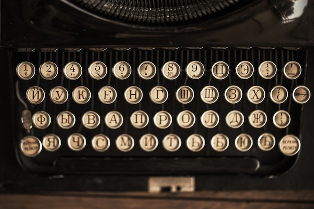 Oude zwarte typemachine met papierwaarde op tafel