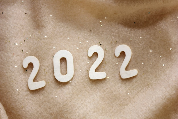 Oudejaarsavond 2022. nieuwjaarsnummer is bekleed met houten cijfers op een beige fleece deken bestrooid met gouden pailletten. gelukkig nieuwjaar