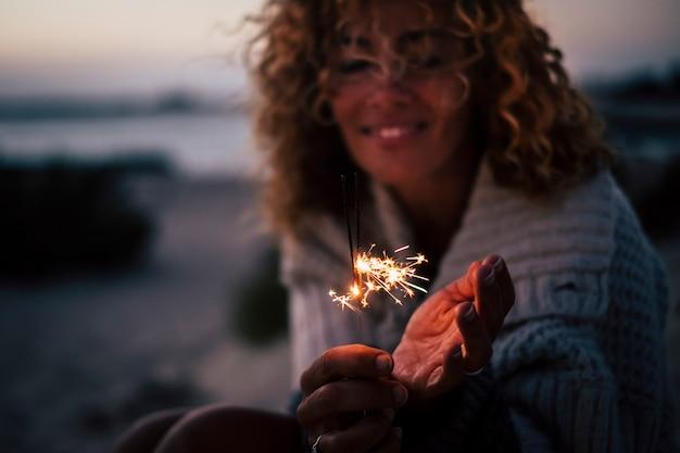 Oudejaarsavond of feesttijd voor vrolijke dame in de avondnacht met vuursterretjes