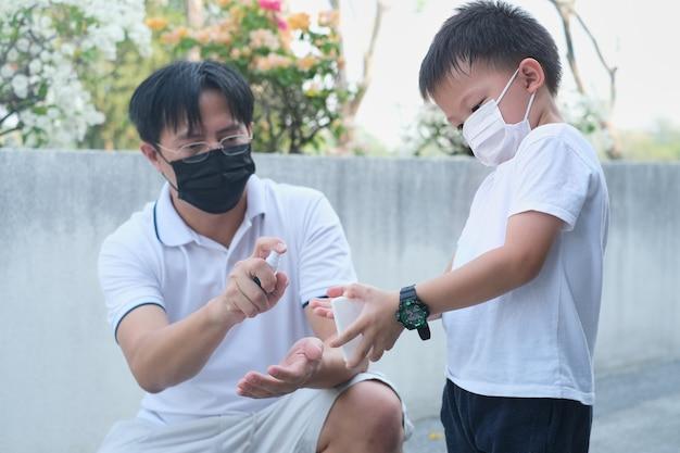 Ouder die de hand van het kind schoonmaakt met handdesinfecterend middel familie met kind dat een beschermend medisch masker draagt in het park tijdens covid19 gezondheidscrisis virus amp ziektebescherming nieuwe normale levensstijl