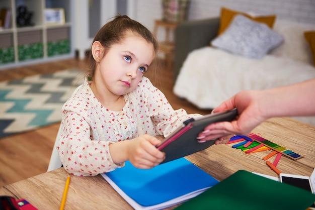 Ouder die de tablet van het kind weghaalt