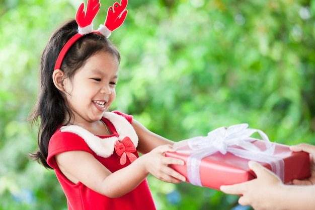 Ouder die kerstmisgift geeft aan leuk aziatisch kindmeisje