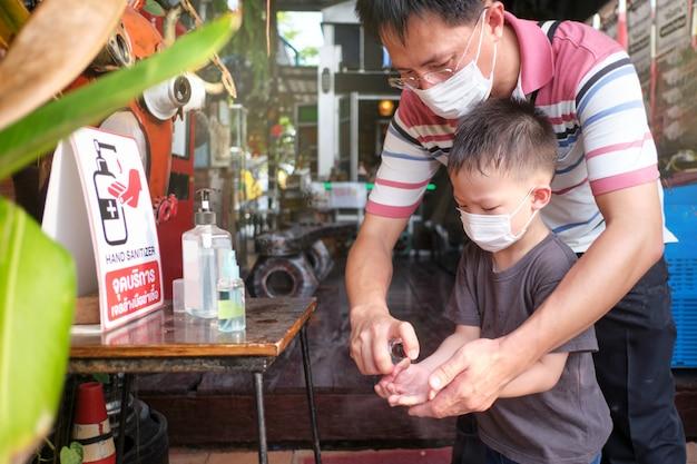 Ouder die kindhand met handdesinfecterend middel schoonmaakt, dan en zoon die medisch masker in openbare plaats dragen tijdens gezondheidscrisis covid-19