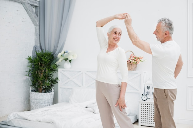 Ouder echtpaar dat in de slaapkamer danst
