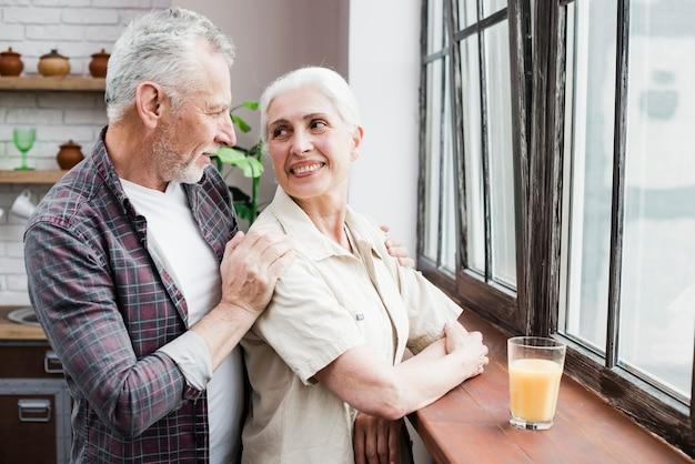 Ouder echtpaar kijkt door het raam