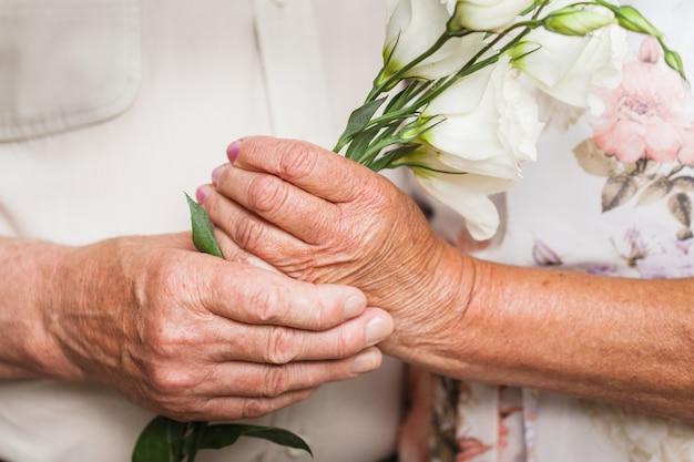 Ouder echtpaar knuffelen en houden van delicate lichte, witte bloemen, liefde zonder grenzen, liefde voorbij de tijd