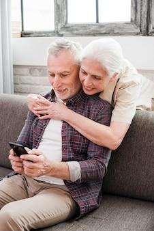 Ouder echtpaar met behulp van een smartphone