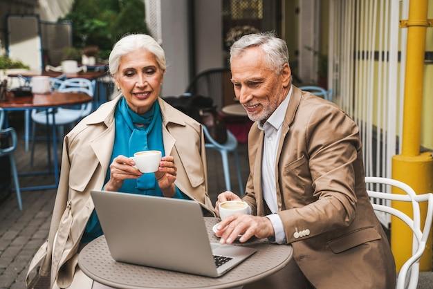Ouder echtpaar met laptop zittend in een restaurant