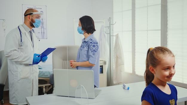 Ouder en arts praten in een medisch kantoor met een beschermend masker tijdens de covid-19-pandemie. arts-specialist in de geneeskunde die medische zorg verleent, consultatiebehandeling in ziekenhuiskast
