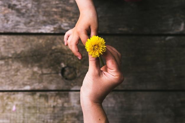 Ouder en kind handen bloemen overhandigen
