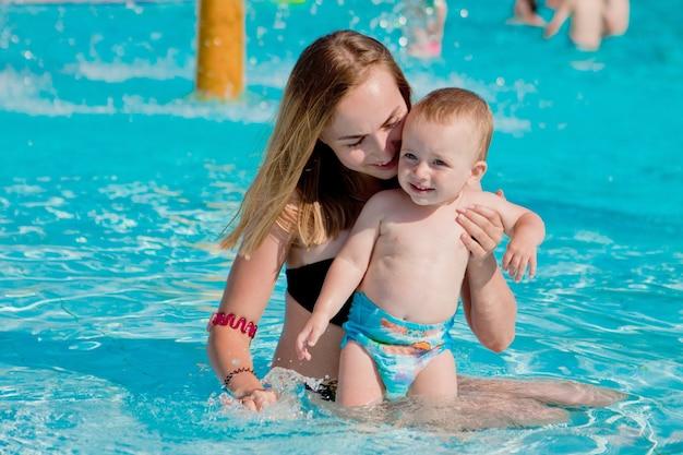 Ouder en kind zwemmen in een tropisch resort. zomer buitenactiviteit voor gezin met kinderen