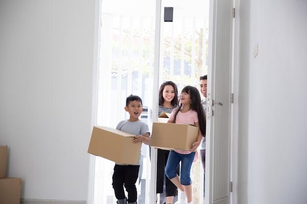 Ouder en kinderen met kartonnen doos. verhuizen naar een nieuw huis