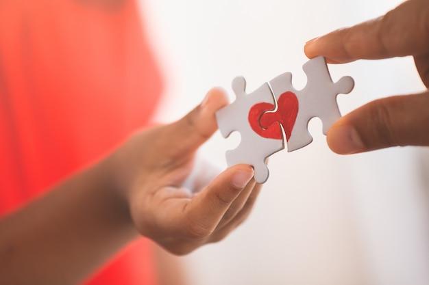 Ouder en kindhanden die het stuk van de paarpuzzel met getrokken rood hart verbinden