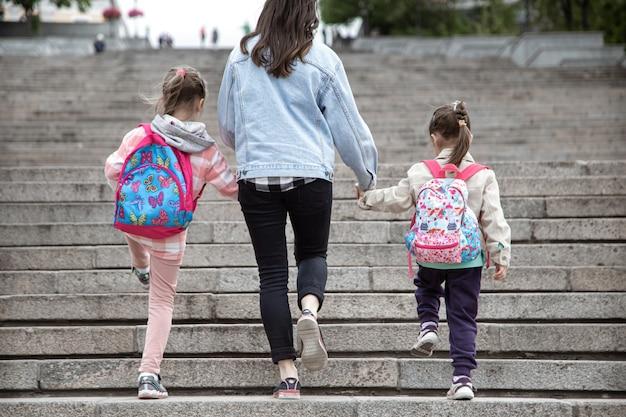 Ouder en leerling van de basisschool gaan hand in hand. moeder van twee meisjes met een rugzak achter de rug. begin van lessen. eerste dag van de herfst.