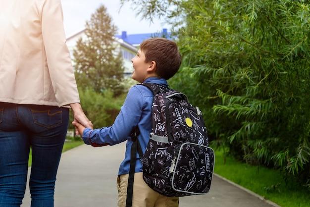 Ouder en leerling van de basisschool gaan hand in hand vrouw en jongen met rugzak achter de rug